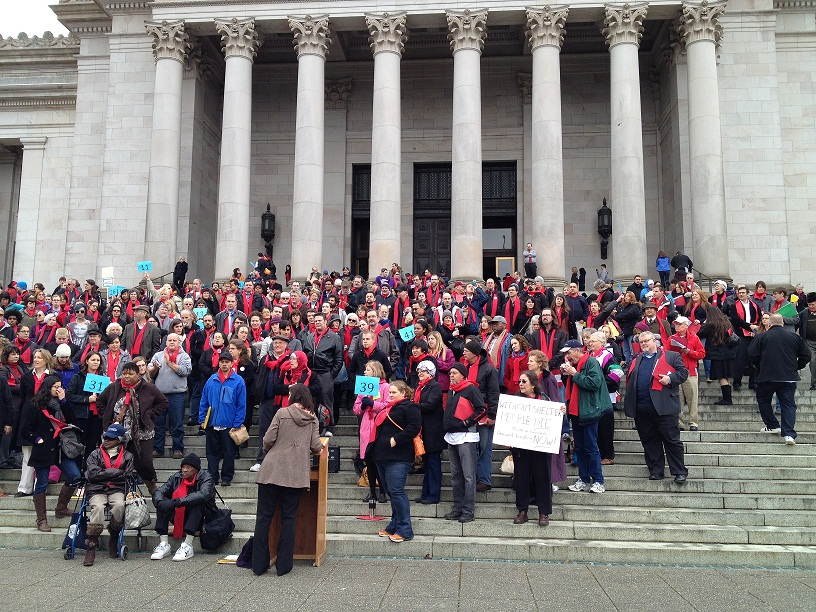 Housing advocates convene on the steps of the state capitol to rally for affordable homes for all.