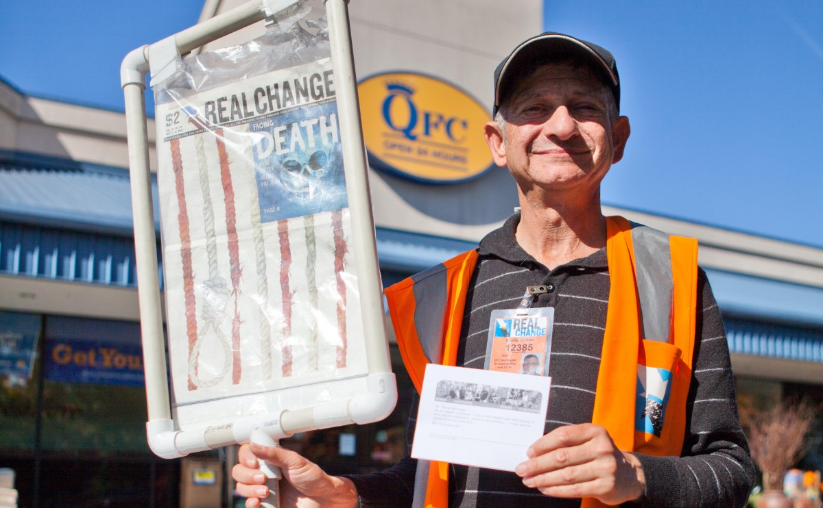 Shelly Cohen has advocated for a number of causes. Here, he holds an advocacy card that customers signed expressing their support for QFC workers during the UFCW 21 Stand With Our Checkers Campaign in  2013. Image credit: Alex Garland.