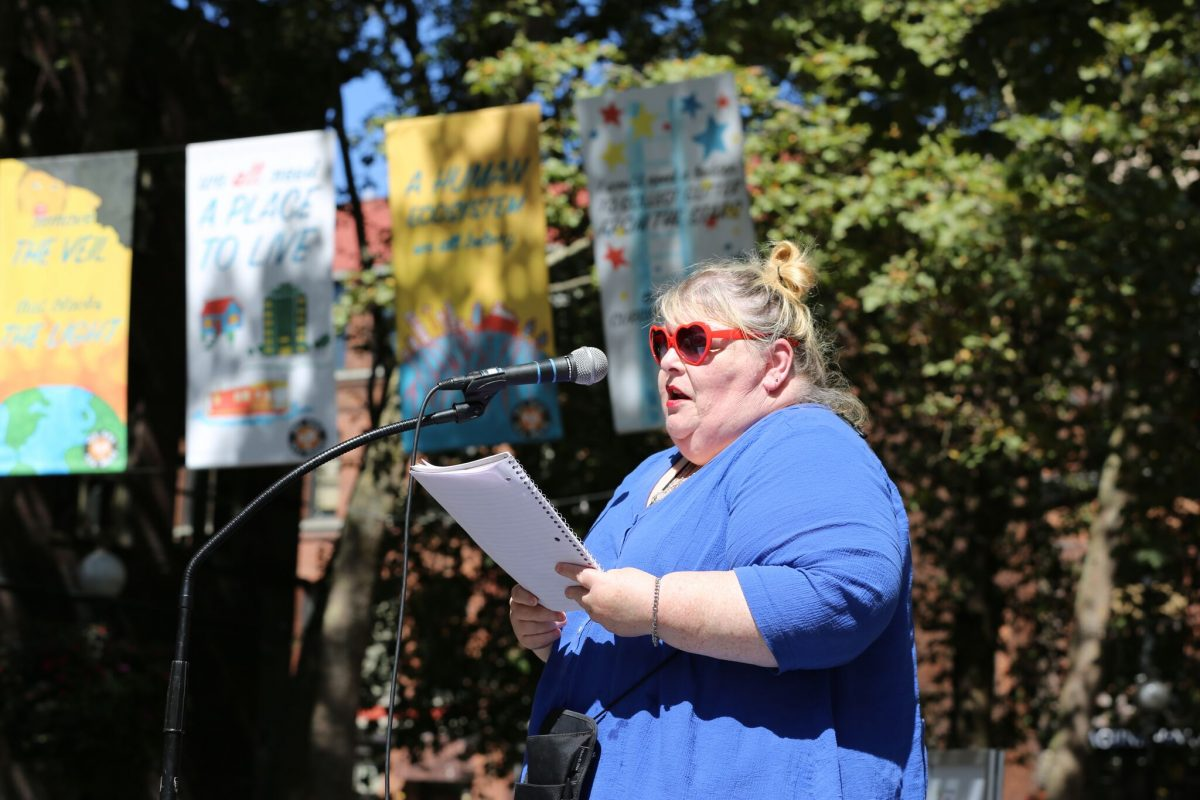 A student artist reading her poem in front of the We Are All Here banner. Photo credit: Path with Art